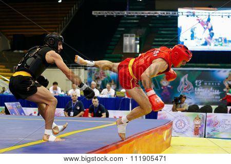 JAKARTA, INDONESIA - NOVEMBER 18, 2015: Nicholas Evagorou of Great Britain (red) fights Amir Fazli of Iran (black) in the men's 85kg Sanda event at the 13th World Wushu Championship 2015.
