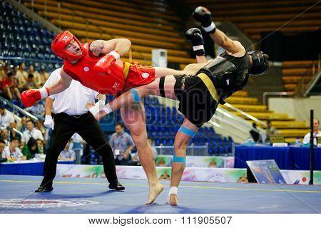 JAKARTA, INDONESIA - NOVEMBER 18, 2015: Robin Larrson of Sweden (red) fights Hamidreza Gholipour of Iran (black) in the men's 90kg Sanda event at the 13th World Wushu Championship 2015.