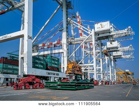 Crane moving containers in port shipyard in to ship