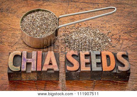 chia seeds in a metal measuring scoop and a text in vintage letterpress printing blocks against rustic wood