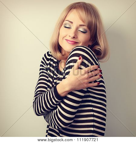 Happy makeup blond woman hugging herself with natural emotion on enjoying face with close eyes. Love concept by yourself. Toned closeup portrait poster