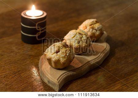 Three salty muffins on wood cut boarding.