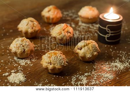Seven salty muffins near candle on wood table.