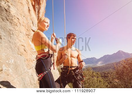 Couple of rock climbers on belay rope