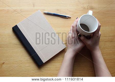 Lady's hands with cofee cup, notebook and pen on the table