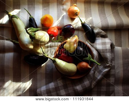 Black and white Aubergines, onions, red paprika set on striped linen cloth