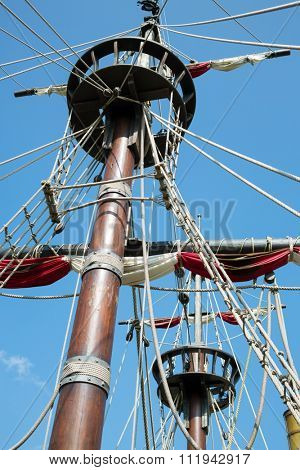 Wooden mast of the ship with rope-ladder and canvas. poster