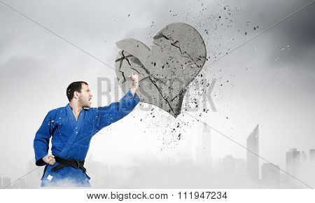 Young determined karate man breaking with hand concrete heart