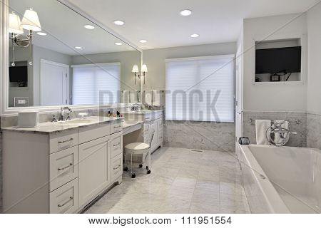 Master bath in suburban home with white cabinetry