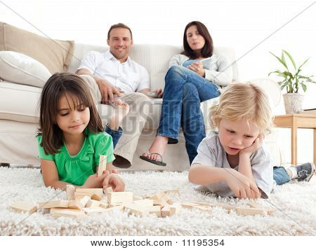 Proud Parents Looking At Their Children Playing With Dominoes On The Floor