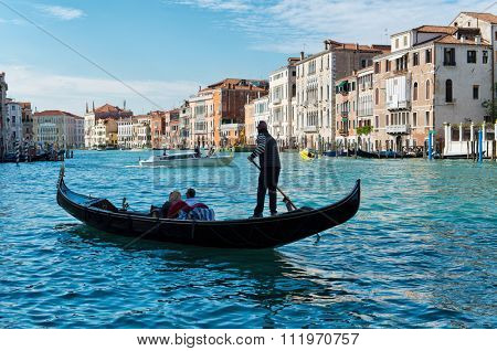 VENICE, ITALY - 17 OCTOBER 2015: Gondolier rowing tourists in his gondola on the Grand Canal in Venice, Italy on 17 October 2015.