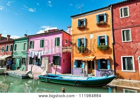 Colorful houses with drying laundry hanging on the facades, Burano, Venice, Italy, painted in bright colors to guide the fishermen home in mist