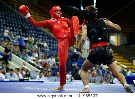 JAKARTA, INDONESIA - NOVEMBER 18, 2015: Shahrbano Semiromi of Iran (red) fights Hergie Bacyadan of Philippines (black) in the men's 65kg Sanda final event at the 13th World Wushu Championship 2015.