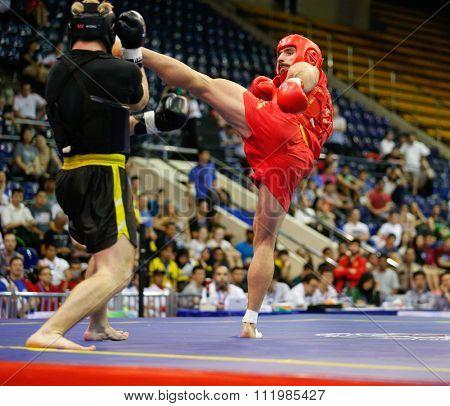 JAKARTA, INDONESIA - NOVEMBER 18, 2015: Amir Fazli of Iran (red) fights Dmytro Batok of Ukraine (black) in the men's 85kg Sanda final event at the 13th World Wushu Championship 2015.