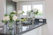 glass vase of flower on black granite counter in classic pantry room poster