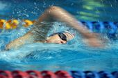 an effects shot of a female freestyle swimmer in action . poster