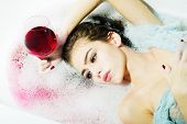 Closeup view portrat of attractive young sexy girl with wet hair lying in white bath tab full of water and soap foam holding drinking glass with red liquid as elixir of beauty or desert wine indoor poster
