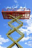 Scissor lift platform with hydraulic system at maximum height range painted in orange and beige colors, large construction machine, heavy industry, white clouds and blue sky on background poster