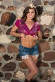 Pretty petite brunette in a purple sequined blouse and denim shorts poster