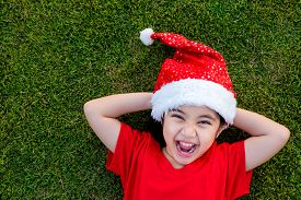 Little Asian girl in santa hat on the green grass