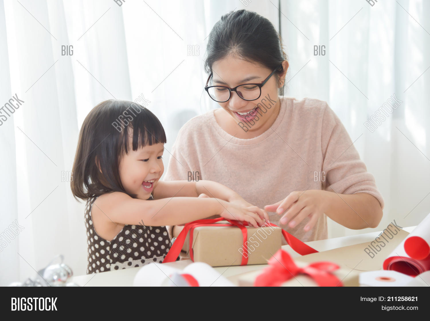 Young Mother And Her Daughter Wrapping A Gift Box For Birthday Christmas New Year In