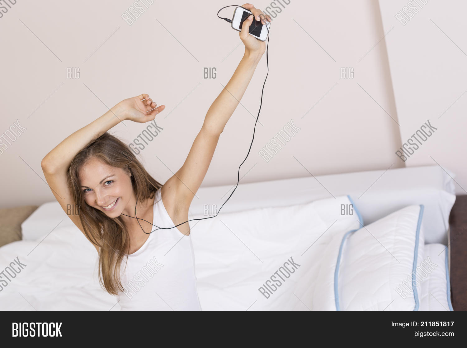 Beautiful cheerful young woman listening to the music wearing pajamas and a  headphones dancing and jumping 9811aefdb