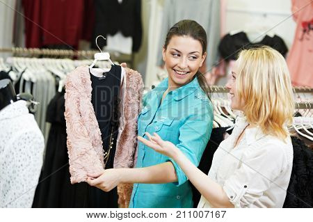 Apparel, clothing shopping. Young woman choosing dress or wear in store