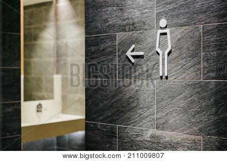 pointer to the toilet. Sign of a male toilet on a concrete wall.