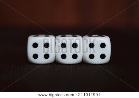 Three white plastic dices in a row on brown wooden board background. Six sides cube with black dots. Tetraphobia unlucky number 4.