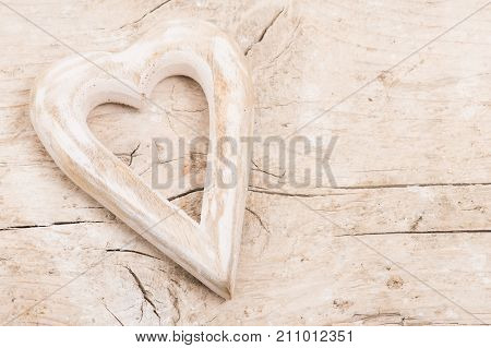 Wooden hart on a pile wooden background