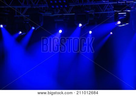 Blue stage spotlights hanging on lighting pipe systems