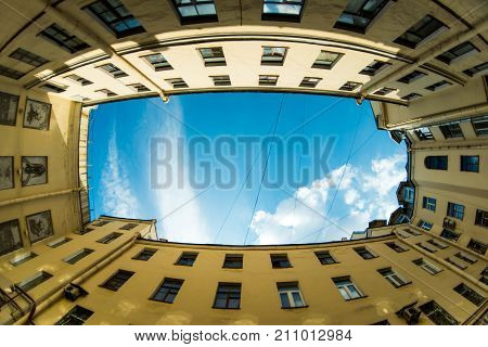 Courtyard city look up with fisheye lens effect. Low angle shot of building with windows and cloudy sky background.