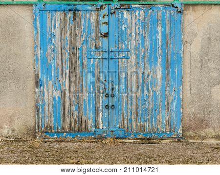 Old blue wooden barn door with paint peeling of