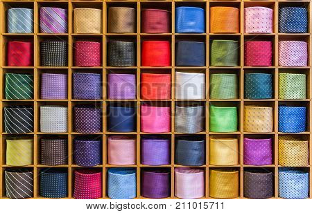Showcase with multicolored ties. View of different colors ties in showcase. Multicolored man. Showcase of rolled neckties at store. Coiled ties on shelf at shop. Twisted neckties beautifully stacked.