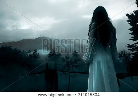 Mysterious Woman in Long White Dress in the Foggy Mountains