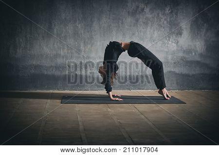 Beautiful woman practices backbend yoga asana Urdhva Dhanurasana - Upward facing bow pose in the dark hall.