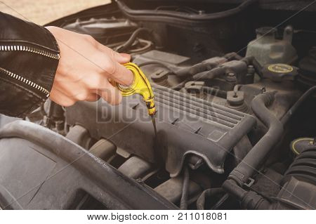 Close-up of the hands The blond girl opens the hood of her car and checks the engine oil level. The concept of car maintenance by women. The concept of a malfunction of the car and its engine