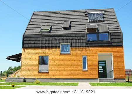 Modern house with energy saving and energy efficiency. Eco-house or wooden eco-home with attic skylights insulation solar panels and solar water heater (SWH) system. Passive House Concept.