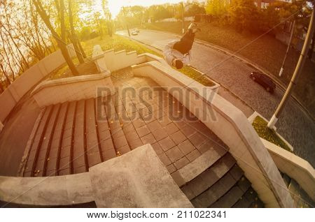A Young Guy Performs A Side Flip In The Autumn Park. The Athlete Practices Parkour, Training In Stre