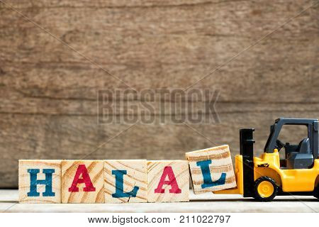 Yellow plastic toy forklift hold letter block L to complete word halal on wood background