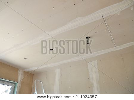 Ceiling construction and repair with drywall board. Building construction gypsum plaster walls and ceiling. Ceiling Joists of Home Under Construction.