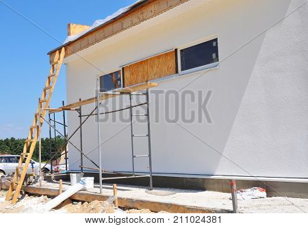 Unfinished house. Home Remodeling and Renovation after Hurricane. Painting house wall with stucco and plastering. Insulation House and Old House Renovation.