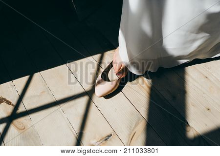 Bride is putting her leg in wedding shoes. Artwork. Close-up