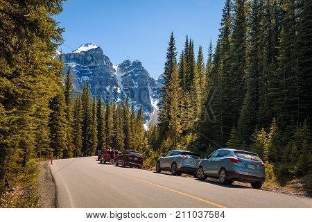 MORAINE LAKE, ALBERTA, CANADA - JUNE 27, 2017 : Cars park along the road to Moraine Lake in Banff National Park, Alberta, Canada, with snow-covered peaks of canadian Rocky Mountains in the background.