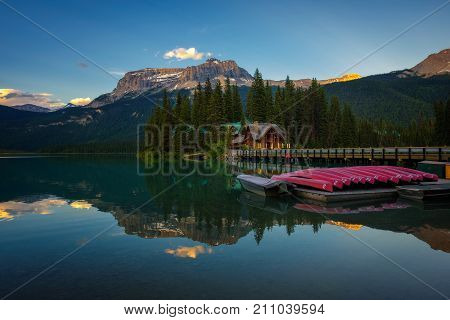 EMERALD LAKE, ALBERTA, CANADA - JUNE 27, 2017 : Canoes on beautiful Emerald Lake with lake lodge and restaurant in the background at sunset, Yoho National Park, Canada.