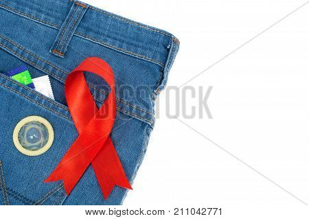 Red ribbon and condom on blue jeans background. Concept of awareness and protection against AIDS, HIV. 1 December. Studio Photo