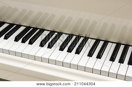 Open white grand piano keyboard close up
