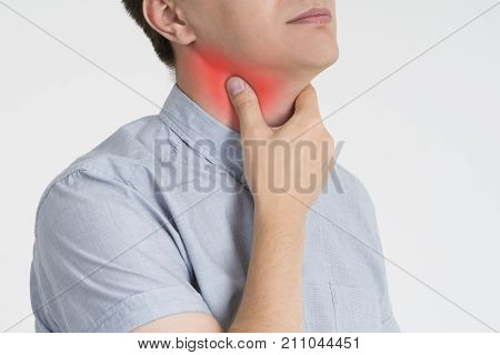 Sore throat men with pain in neck gray background studio shot