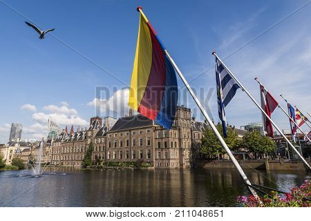 The Hague The Netherlands - August 6 2017: Parliament buildings of the Netherlands some flags of the provinces and in front the pond 'the Hofvijver'.