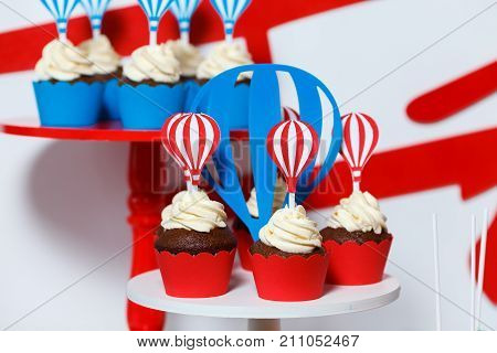 Candy bar on boy's birthday party with a lot of different candies popcorn beverages and big cake. Decorated in bluered and white colors balloons or aviation theme indoor poster